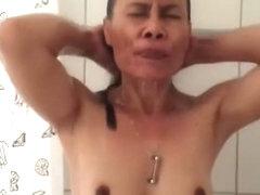 Asian woman with dark nipples and aureola showering