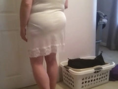 putting on her girdle, under garment over her big tits,