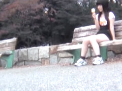 Upskirt and downblouse of girl eating ice cream on the bench