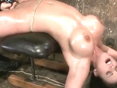 Cute girl with massive tits, bound & oiled Pussy flogged, fingered, made to cum over & ove.
