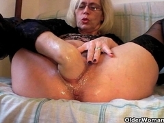 Lewd grandma in nylons fists her curly pussy