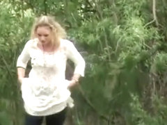 Blonde pees outdoor in nature