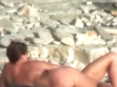 Hot cougar is lying on sand in naked beach video