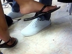 Ebony girl dangling flip flops at lunch