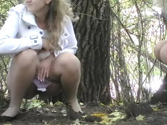 Bride pissing next to tree