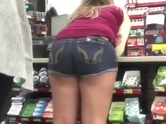 Teen in shorts bent over store counter